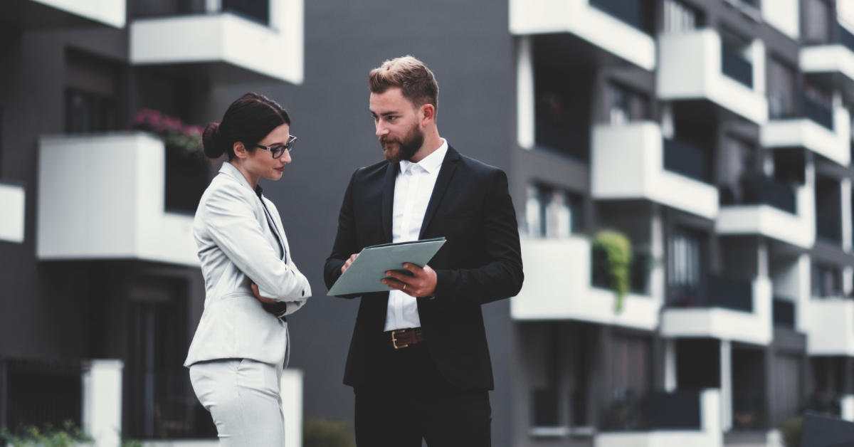 real estate agents discussing in front of building