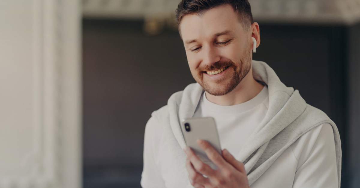 man looking at phone with airpods in