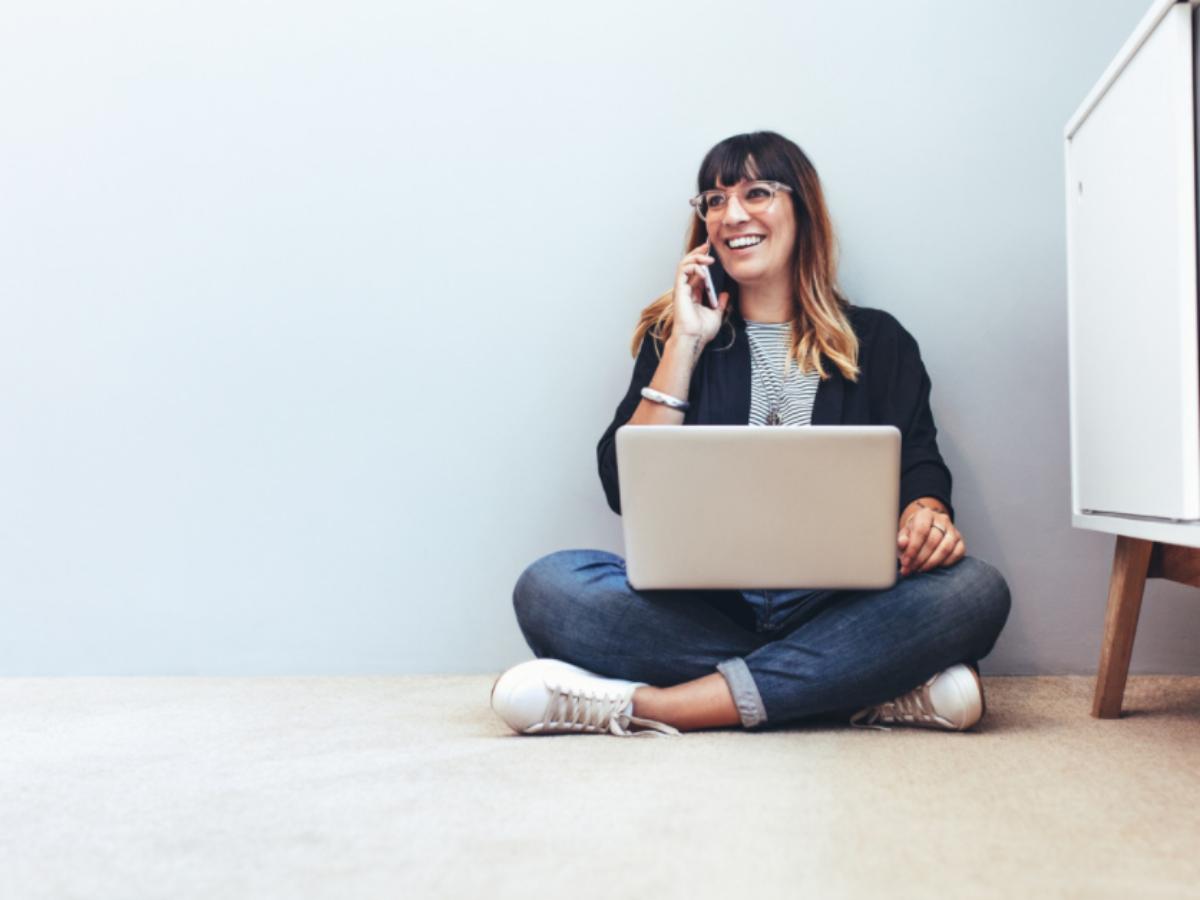 woman on laptop talking on phone